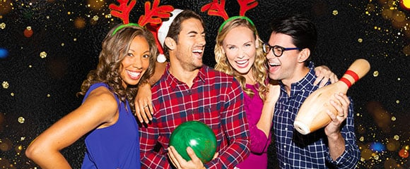 Four friends laughing together in holiday themed clothing holding a bowling ball and pin