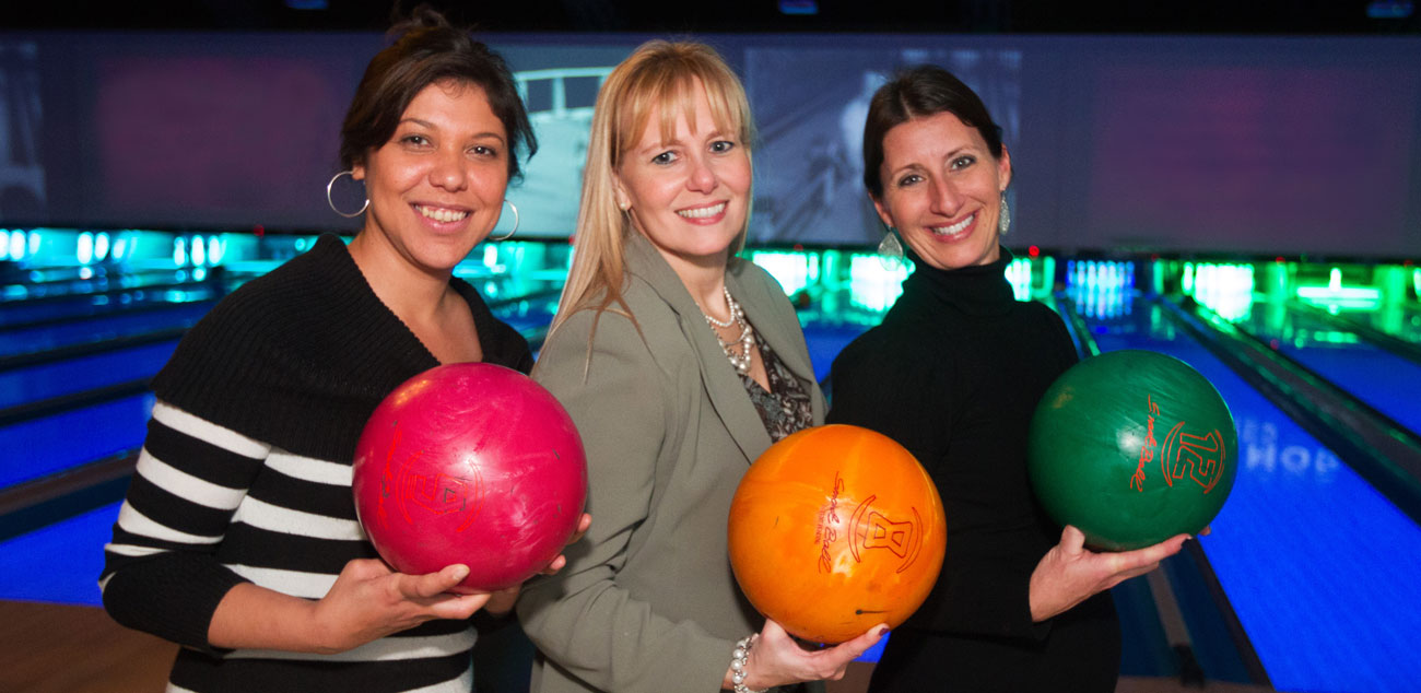 Gillian and two teammates holding bowling balls and smiling