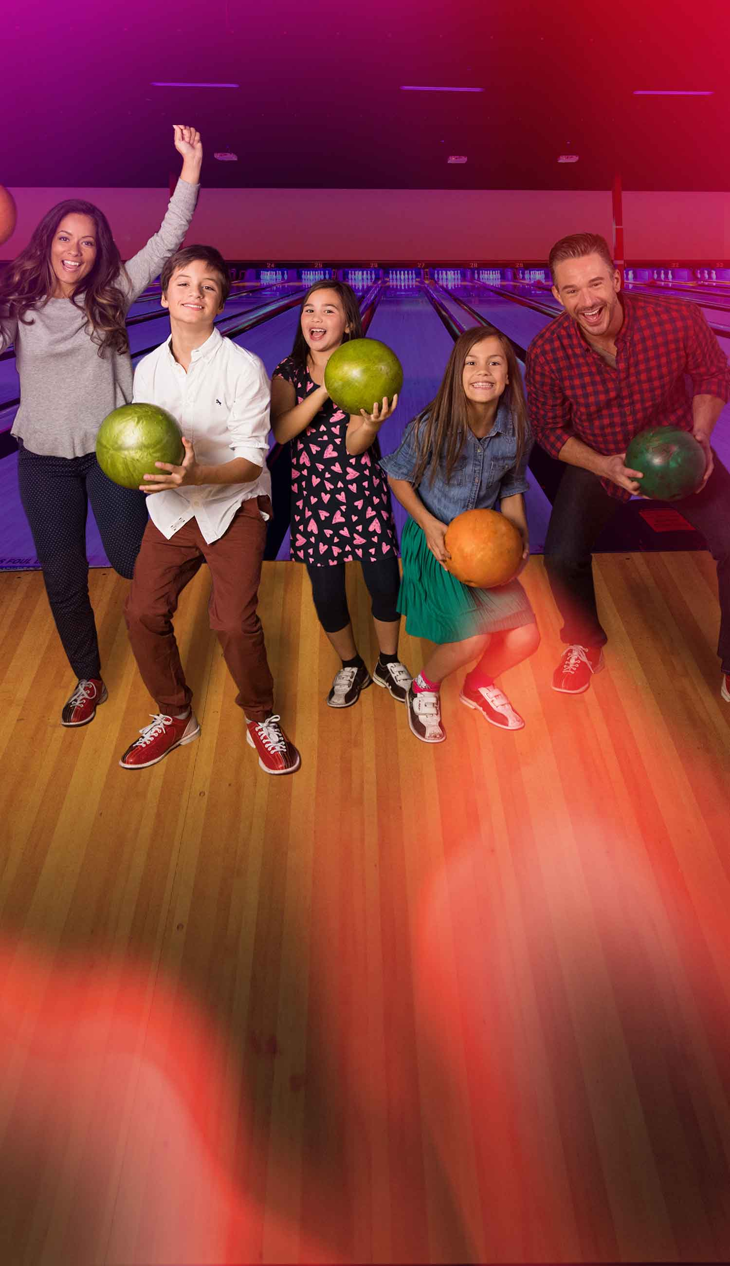 Family on the lanes holding bowling balls