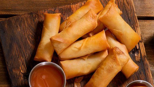 Veggie spring rolls with dipping sauce on a wooden serving tray