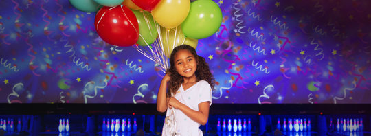 little girl holding balloons in front of a bowling alley