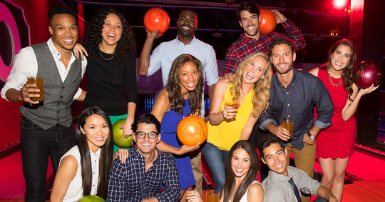 group of friends with drinks and bowling balls