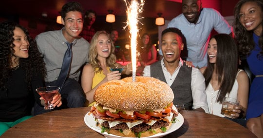 friends crowded around a giant burger with sparklers shooting out of it