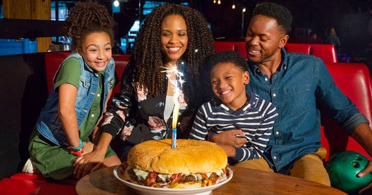 family sitting around a six-pound behemoth burger lit with sparklers