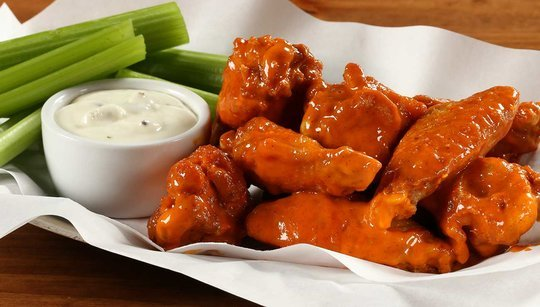 Pile of buffalo wings next to a cup of ranch dressing and celery sticks