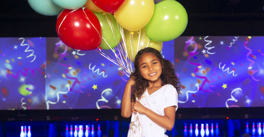 Girl holding a bundle of balloons on the lanes