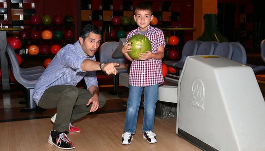 Dad showing son how to bowl