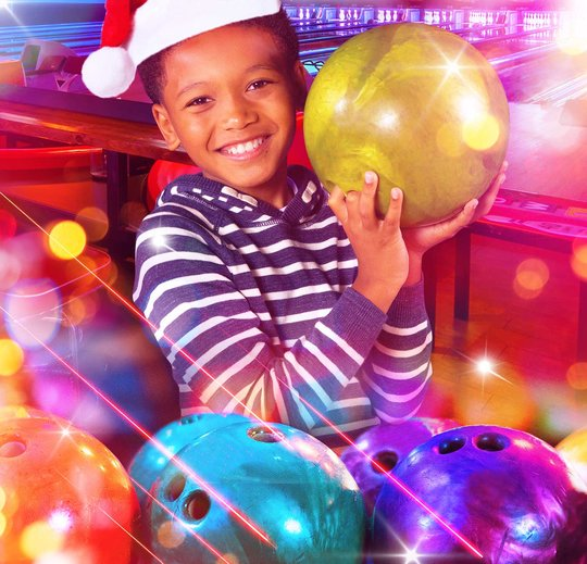 Child holding a bowling ball wearing a santa hat