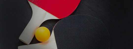 two ping pong paddles and a ball