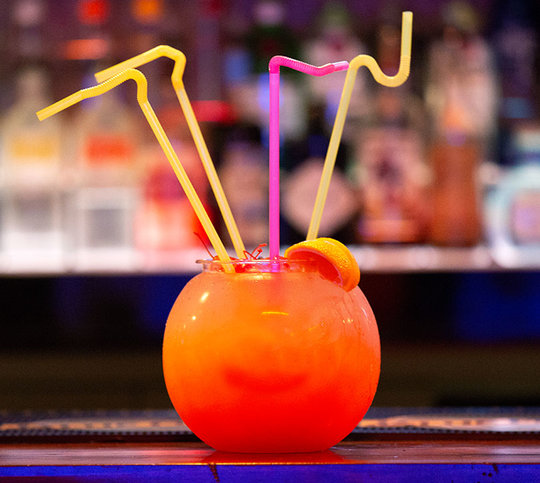 Bright orange drink in a fishbowl with crazy straws in it
