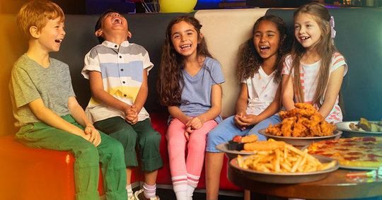 kids sitting on couch next to a table with pizza, wings, and French fries