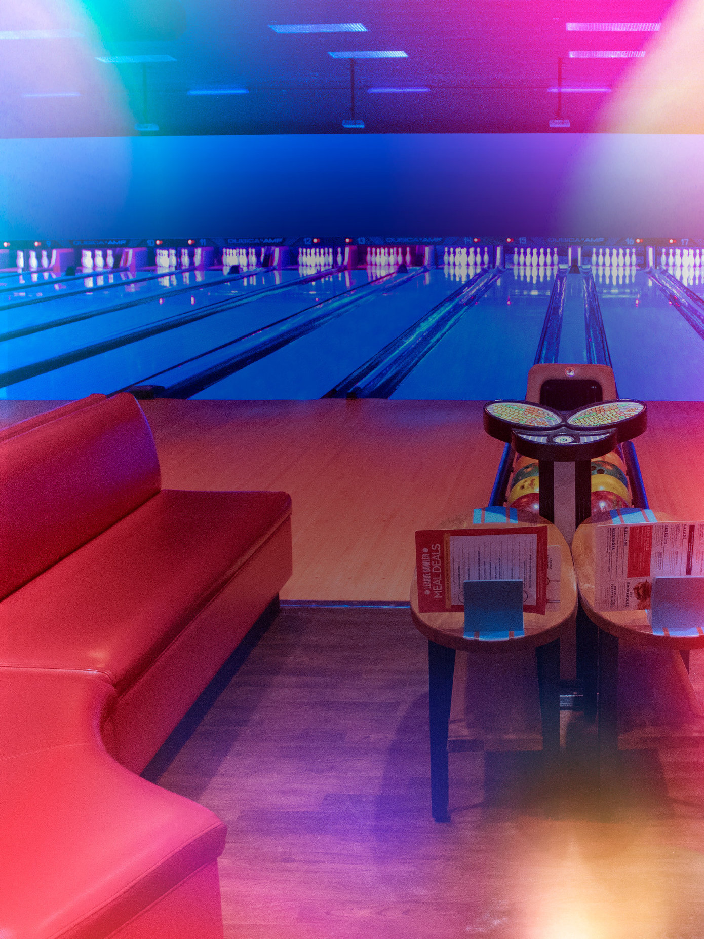 front view of bowling lanes with red plush couches