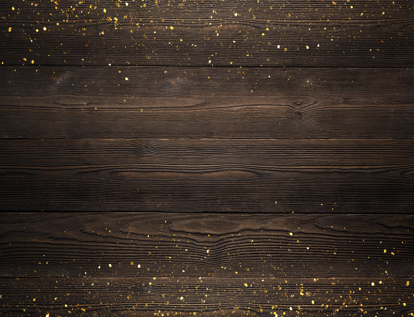 Gold glitter on top of a dark brown wood background