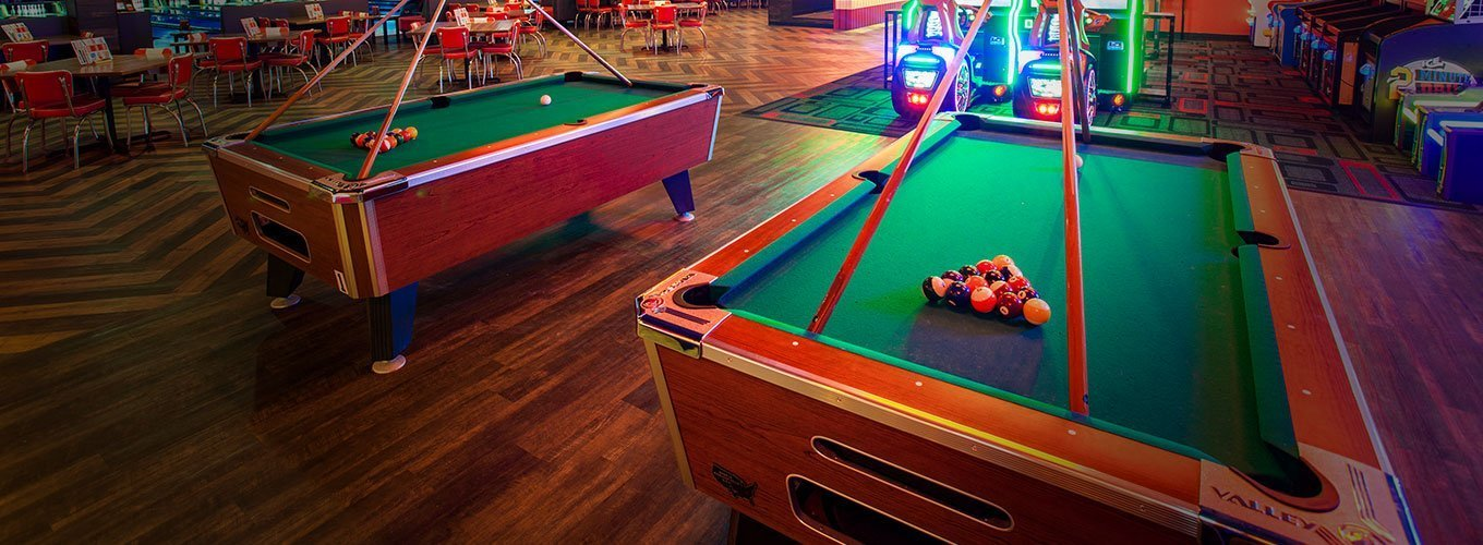 Billiards table with balls racked and cues above