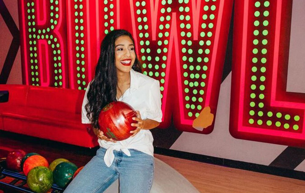 Young woman holding a bowling ball and posing in front of a Bowl Sign