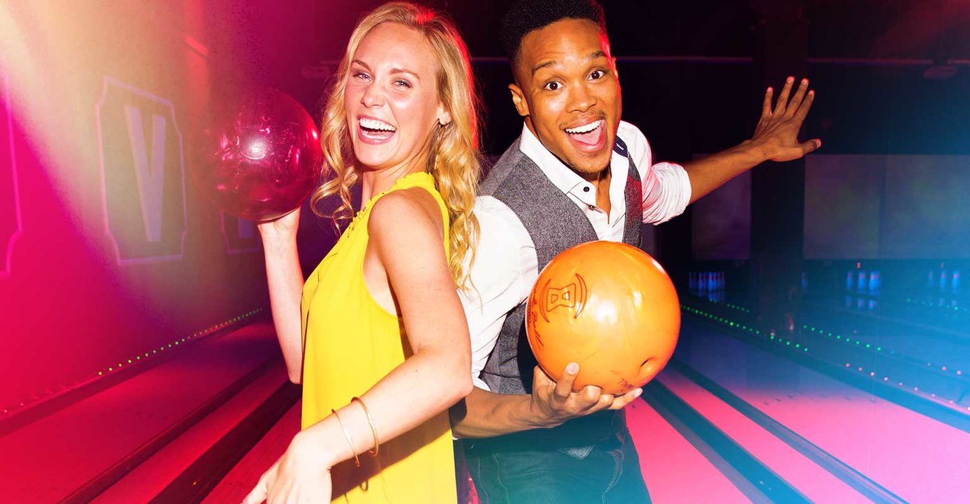 Two people holding bowling balls in front of lanes