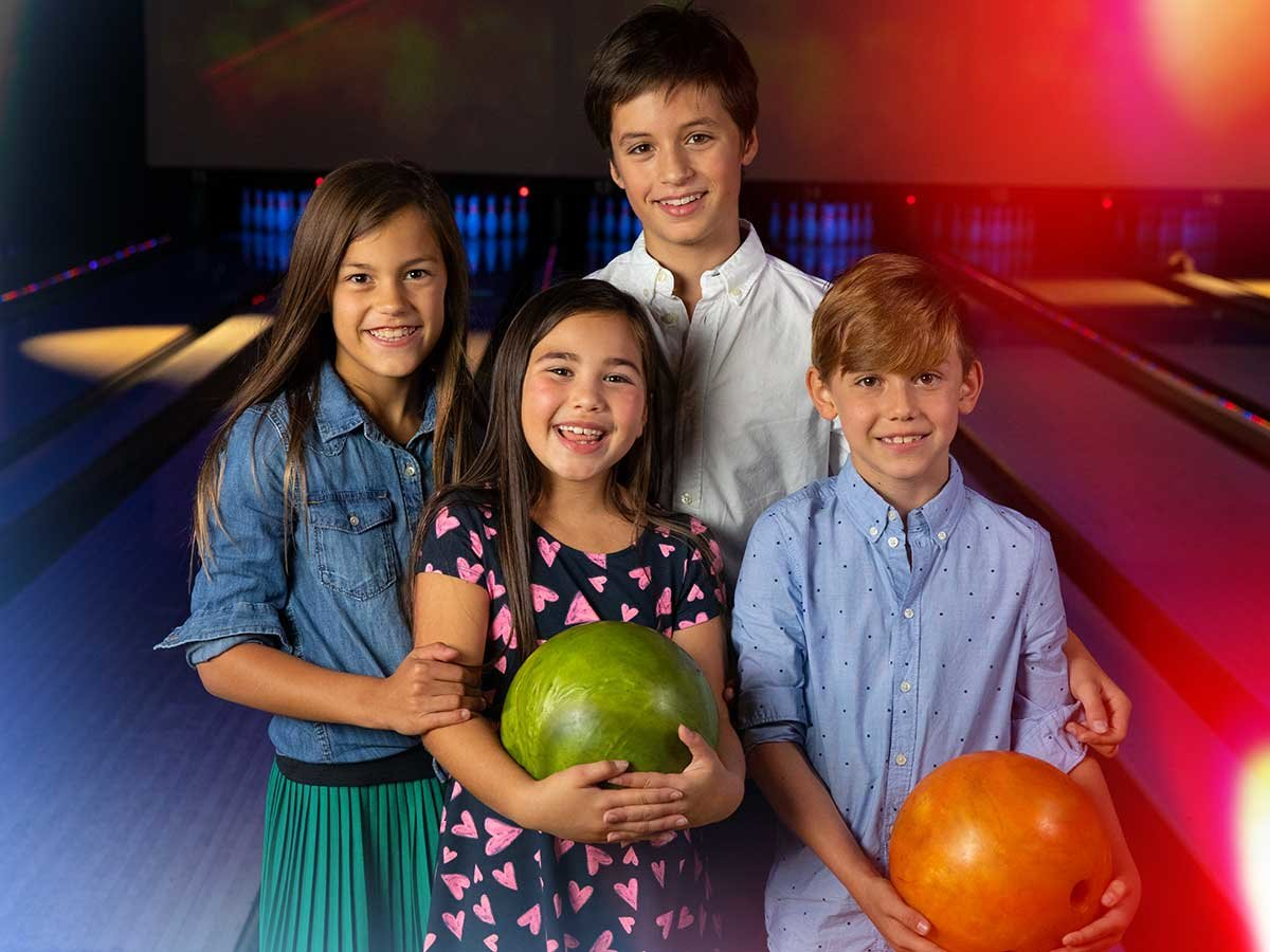 Kids in front of lanes smiling