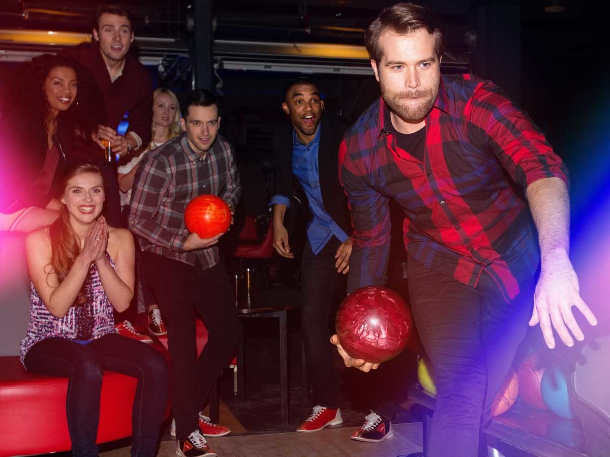 Man bowling in front of group